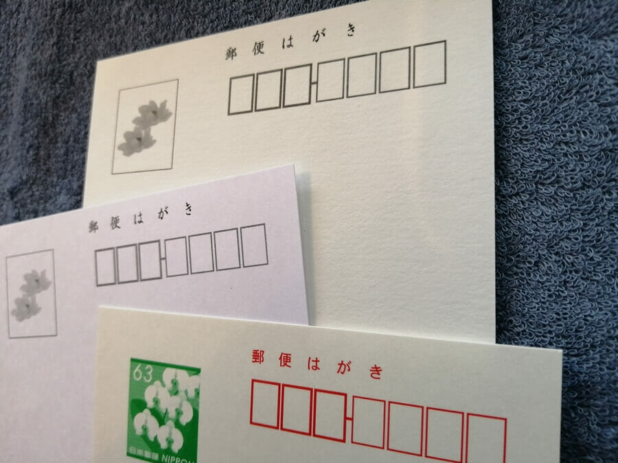 おたより本舗の写真入り喪中はがき、台紙3種の表面を比較した画像(奥から順に大礼紙、ケント紙、郵便はがき)