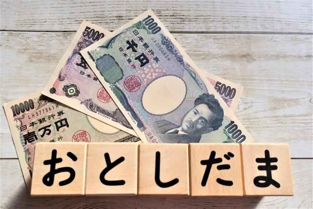 「おとしだま」と書かれた木製ブロックを日本の紙幣とコイン